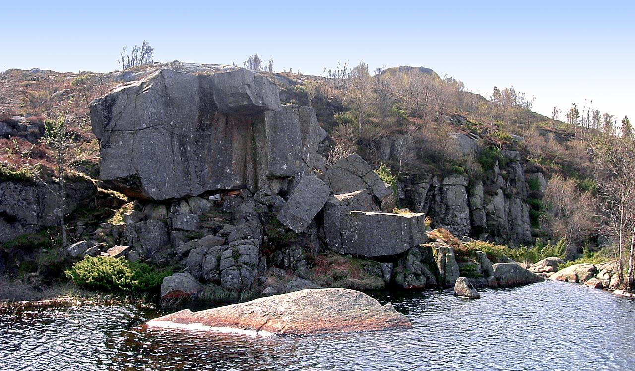 Mysinghålå sett fra andre siden av det lille vannet ved stedet. Inngangen er midt i bildet, under den store steinblokka.