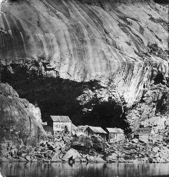 Foto av tre hus under helleren midt på 1800-tallet. Foto: Ukjent. Sokndal Bygdetun.