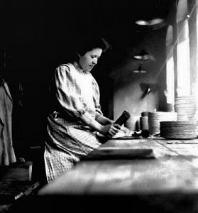 Kvinnelig arbeider presser trykkdekor på tallerkener, cirka 1908